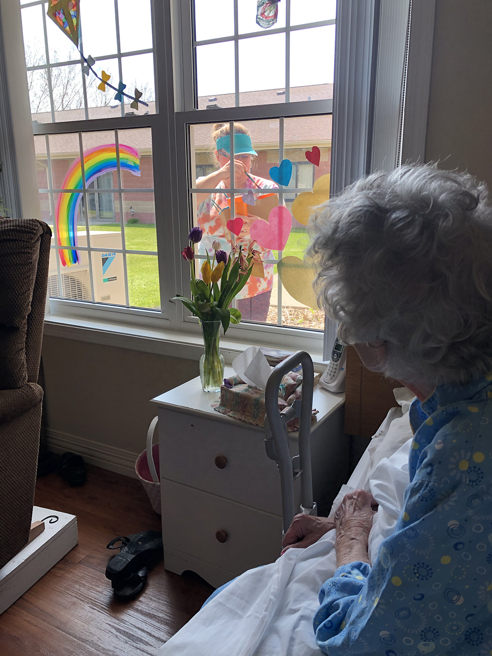 Art teacher Mindi Lill paints on the window of an elder during Covid-19; Maple Manor Care Center/Northern Lights Arts Council, Langdon, ND
