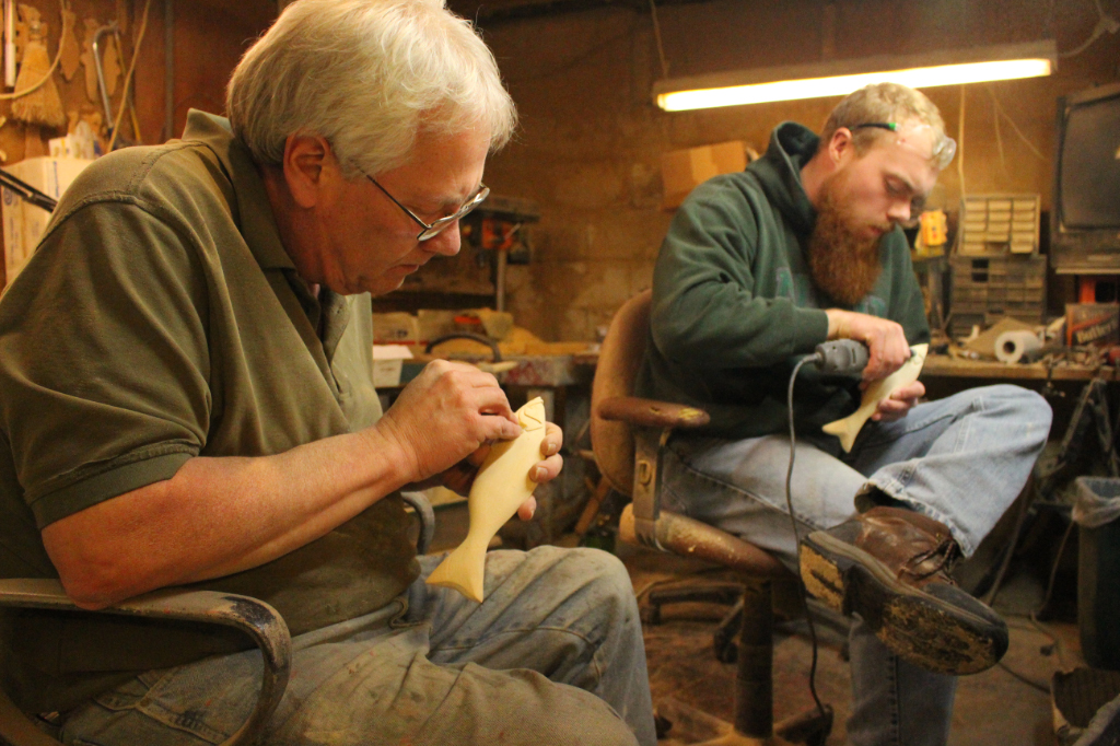 Rick Whittier and his apprentice working on carving fish decoys