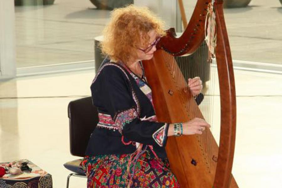 Photo of Debi Rogers playing the harp