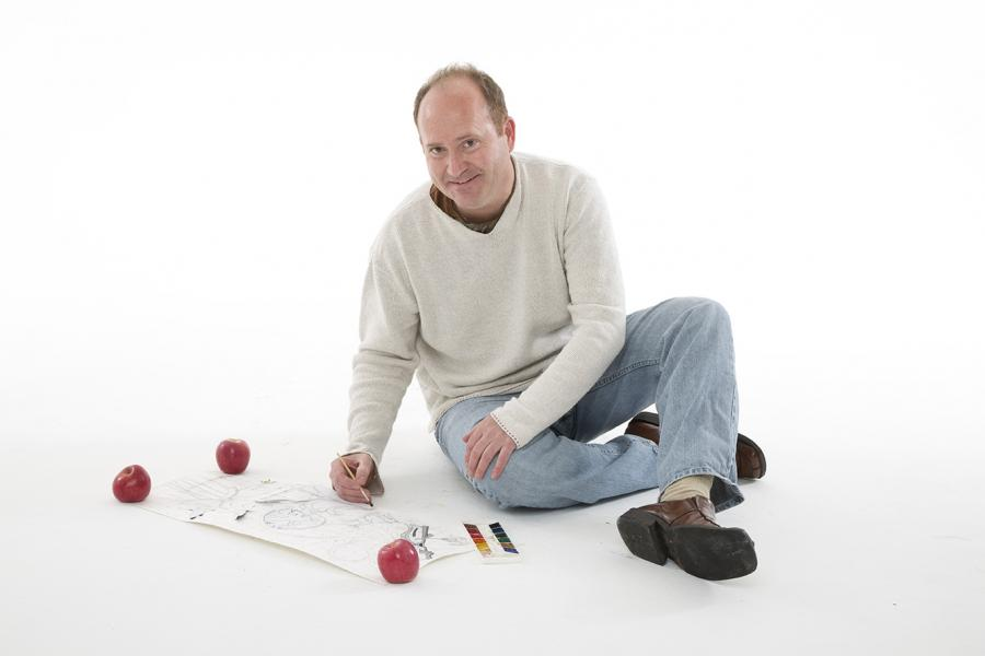 Photo of Markus Tracy sitting on the floor and drawing on paper