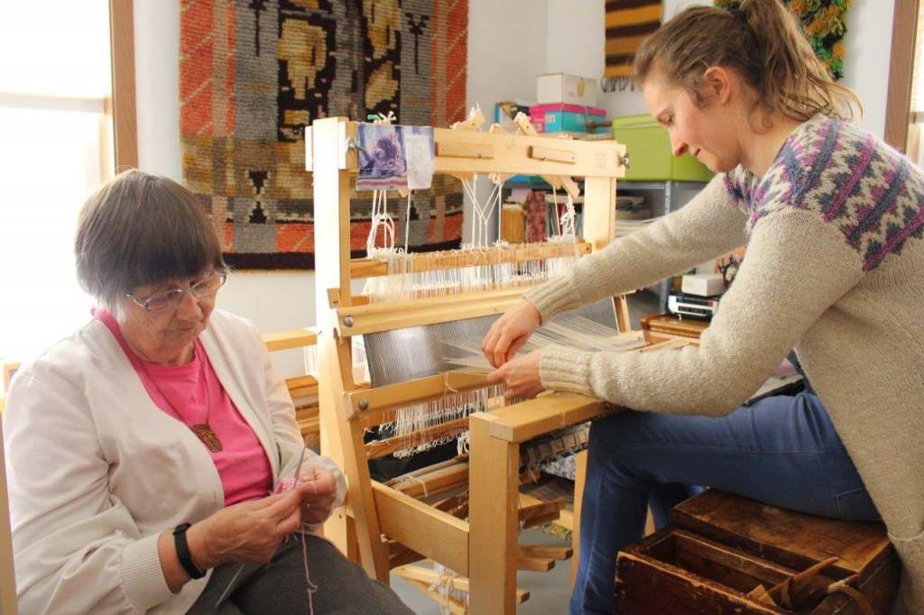 A photo of Finnish weaving master Annikki Martilla of Frederick, SD, and apprentice Sky Purdin of West Fargo, ND weaving together.