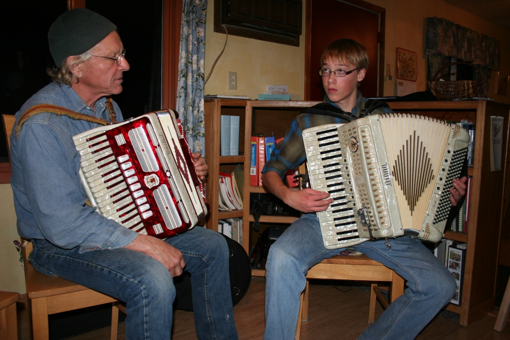 A photo of Master accordionist Chuck Suchy with apprentice Johan Stenslie, both of Mandan, ND playing accordians.